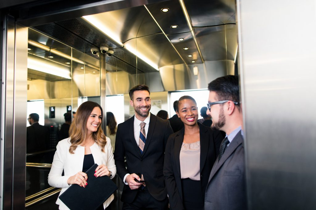 A group of business executives talking in an elevator smiling