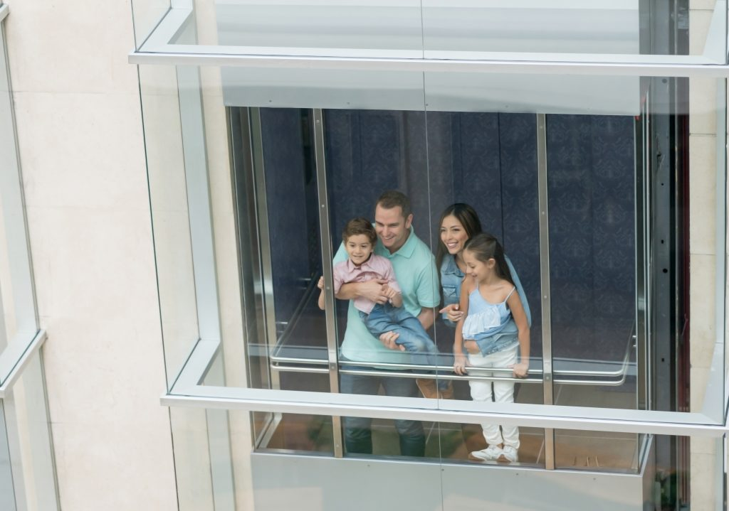 Happy Latin American family using the elevator at the mall and looking through the window