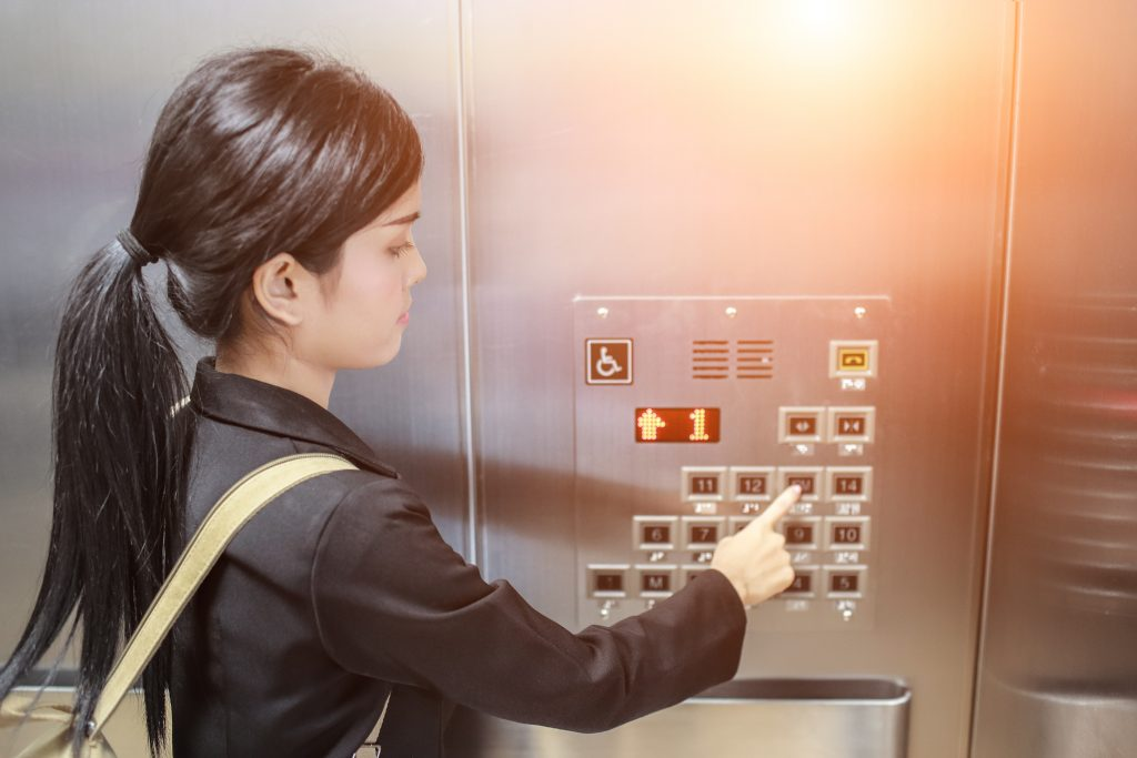 businesswomen pressing elevator button with sun light effect. businesswomen is in elevator.